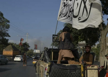 Taliban fighters travel on a vehicle mounted with the Taliban flag in the Karte Mamorin area of Kabul city, Kabul on 22 August 2021. (Photo by Hoshang Hashimi / AFP)